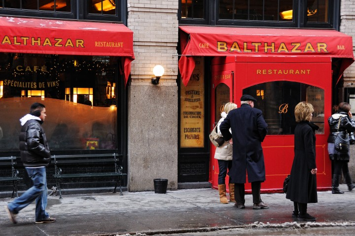 Exterior of New York's Balthazar Restaurant, displaying a red awning with gold lettering