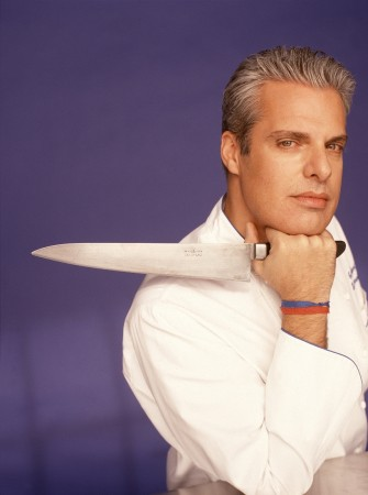 Eric Ripert, chef, resting his chin on his right hand, which is holding a large kitchen knife pointed over his right shoulder.