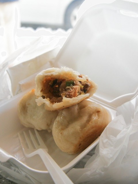 Three dumplings in a to-go container.