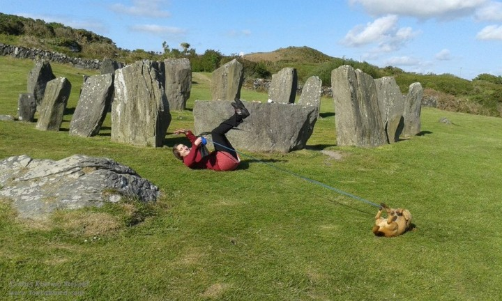 woman and dog gleefully rolling in the grass at Drombeg Stone Circle