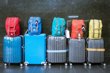 5 wheelie bags with backpacks sitting on top