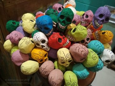 A large container full of colourful papier-mâché maracas, decorated like Día de Muertos skulls.